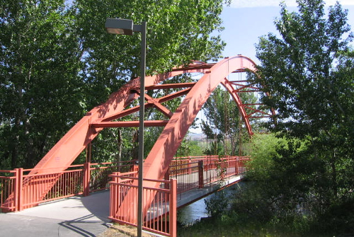 A red iron pedestrian bridge over the Boise River connecting the Greenbelt paths