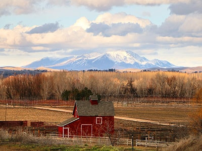 Farm and field in Meridian with snow-capped mountains in the background