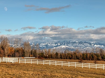 Looking over the foothills at a snow covered mountain range in Star Idaho